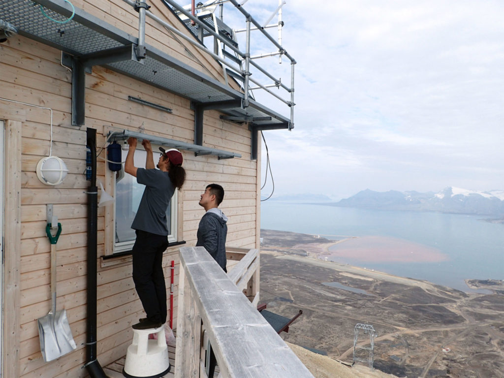 Jun Uetake, left, and Yutaka Tobo install sampling lines for data collection at a research station in Svalbard, Norway.
