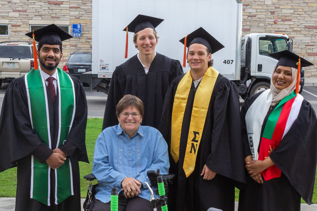 New CSU mechanical engineering alumni - Younis Al Masoudi, Drew Caldwell, Billy Anthony and Shura Al Maawali - delivered a modified wheelchair to Fort Collins resident Wanda Roche at graduation May 17.