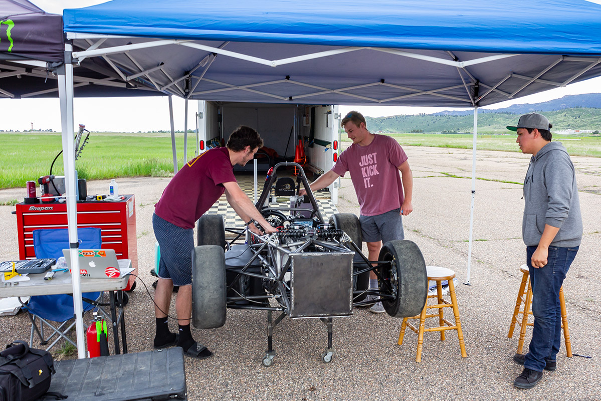 Mechanical engineering graduates work on Ram Racing vehicle they designed.