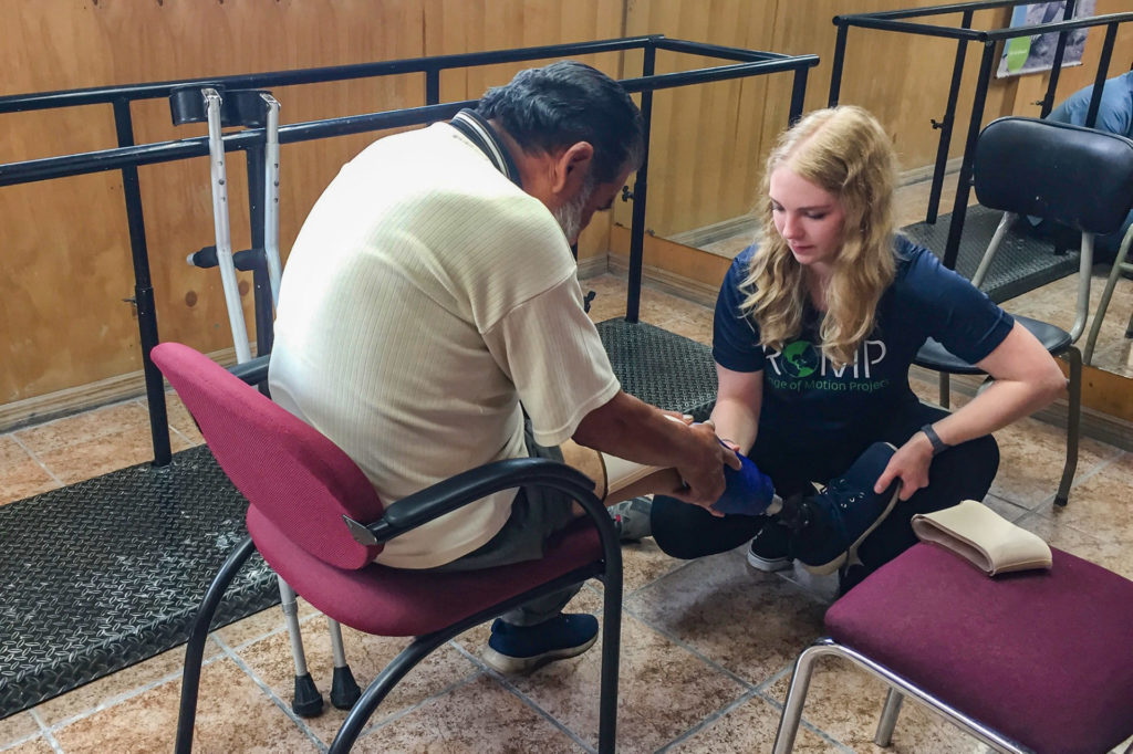 CSU biomedical and electrical engineering student Katie Brown works with a patient to fit a prosthetic device in a clinic in Quito, Ecuador. Photo courtesy Ellen Brennan-Pierce