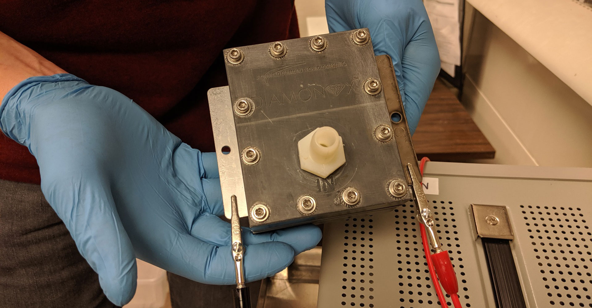 researcher holding an electrochemical cell
