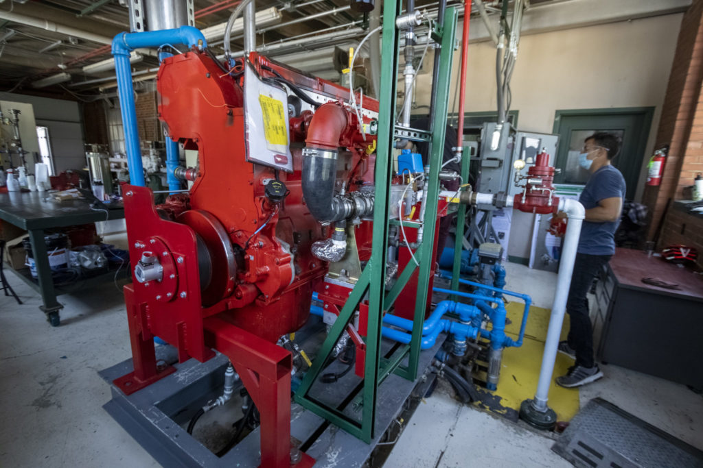 A student works next to a big red Cummins engine at the CSU Powerhouse campus.