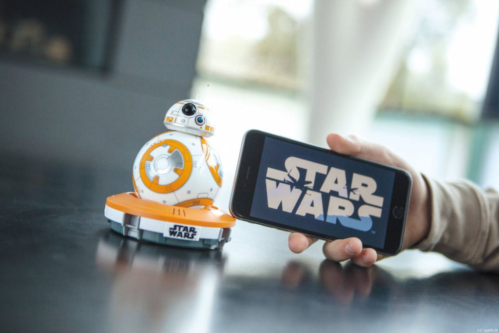 "Robot BB-8 controlled by a cell phone with the words ""Star Wars"" on the screen."