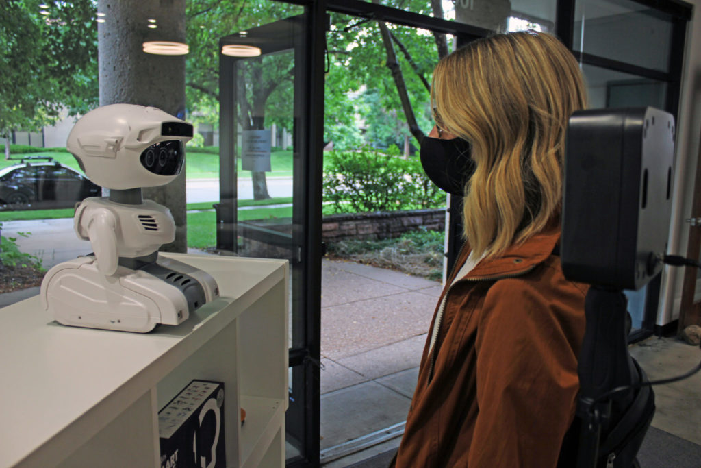 Misty the robot in a lobby testing the temperature of a woman