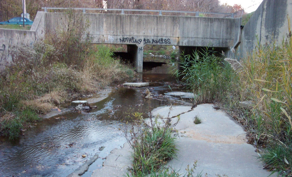 A photo showing stream flow in an urban watershed going under a bridge.