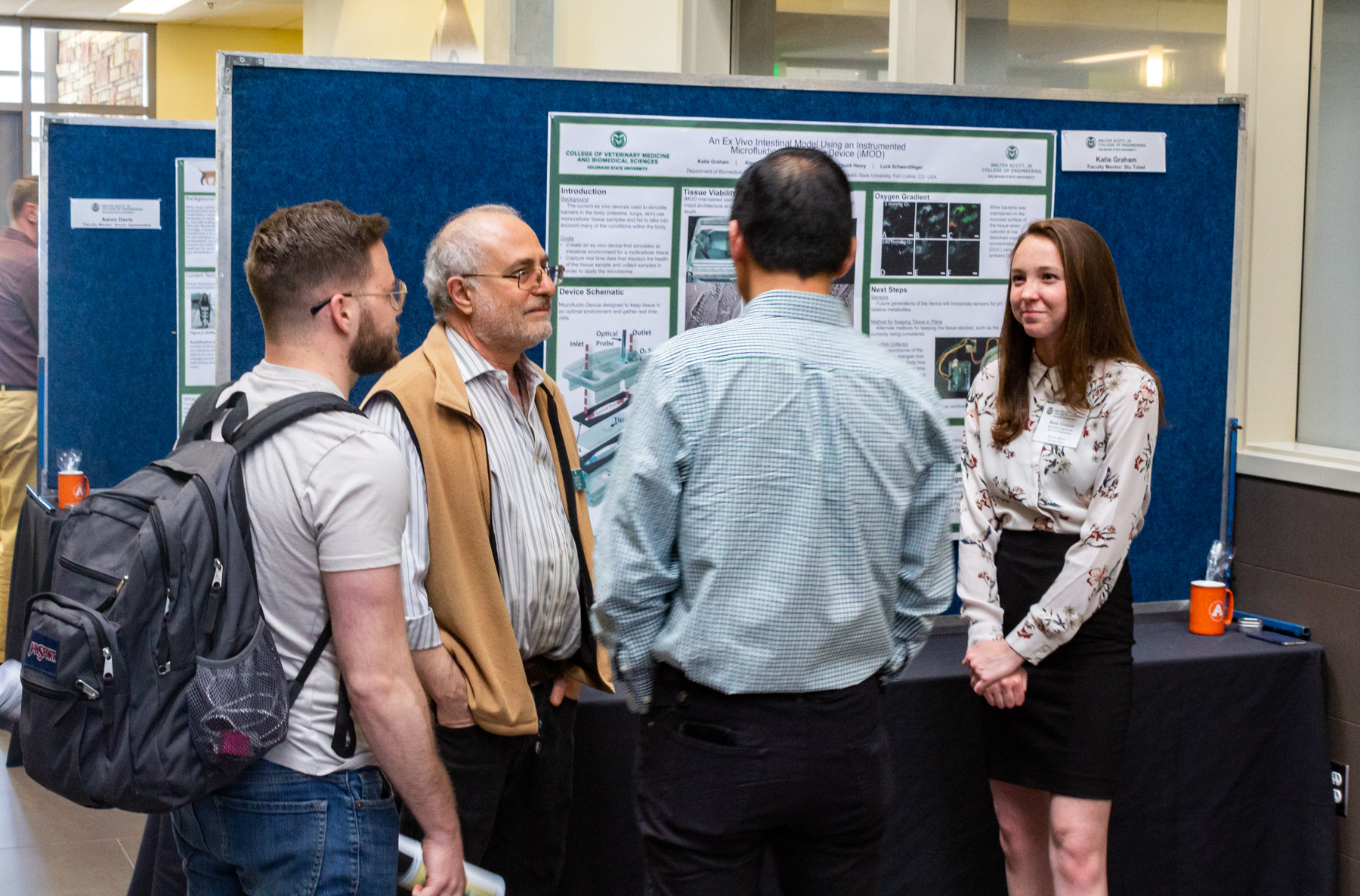 Scott Undergraduate Research Experience (SURE) program student Katie Graham discusses her project at the 2019 SURE Poster event with SBME Director Stu Tobet and other students.