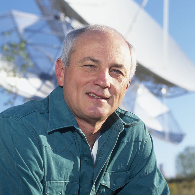 Picture of Tom Vonder Haar, Emeritus University Distinguished Professor in Atmospheric Science, sitting in front of a satellite dish