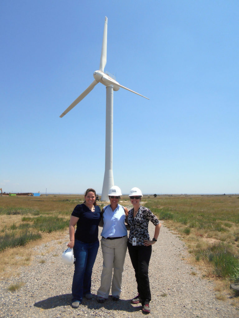Ellison, middle, flanked by two co-workers in front of a wind turbine at the National Renewable Energy Laboratory.