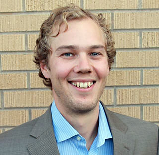 Portrait of Ben Choat, civil engineering doctoral student, standing against a brick wall.