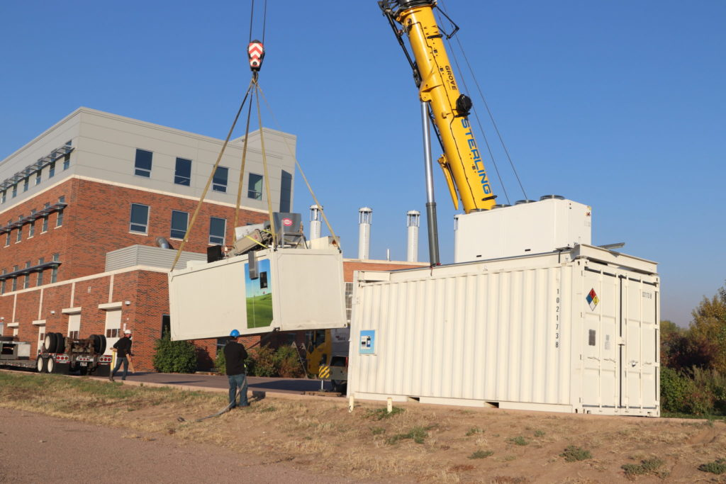 A crane lifting large crates that make up the state's first public hydrogen fuel station in front of the CSU Energy Institute.