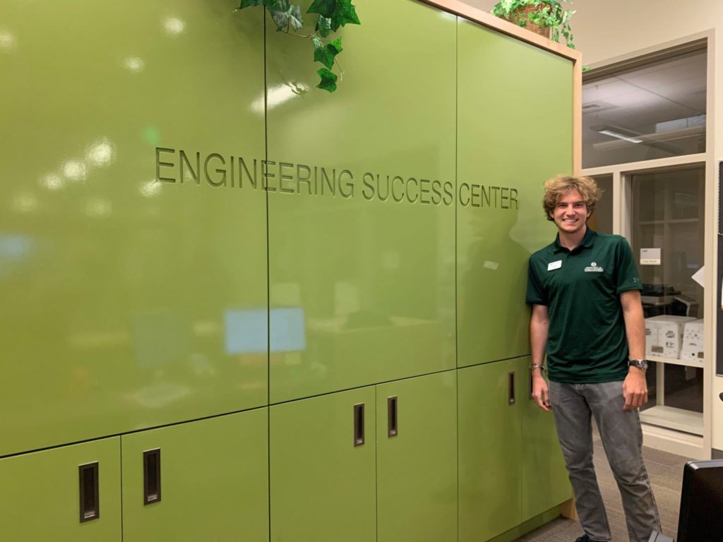 Jared Licht, an Engineering student standing next to a green wall in the Academic Success Center.