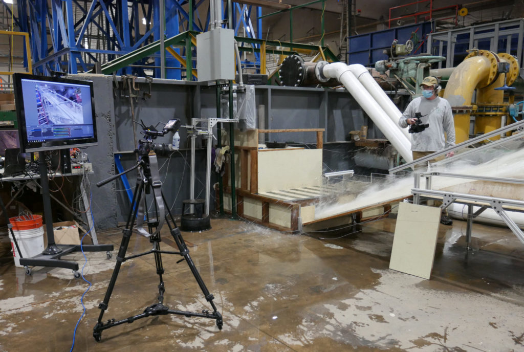 Associate Professor Chris Thornton uses a video camera to give stakeholders a close-up view as water rushes down the spillway model at CSU's Hydraulics Lab. Real-time data from the model is displayed on the screen on the left.