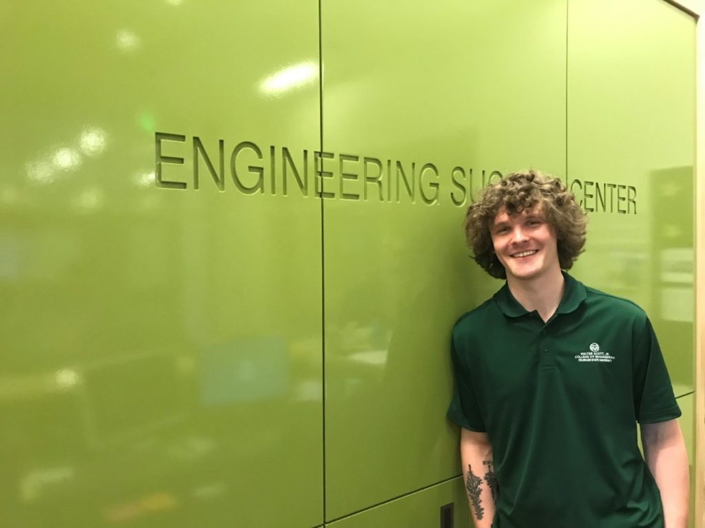 Tyler Nobles, an Enginering student standing in front of a green wall.