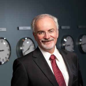 Portrait of Michael Henderson, CSU civil engineering alumnus, in front of a gray wall with clocks.