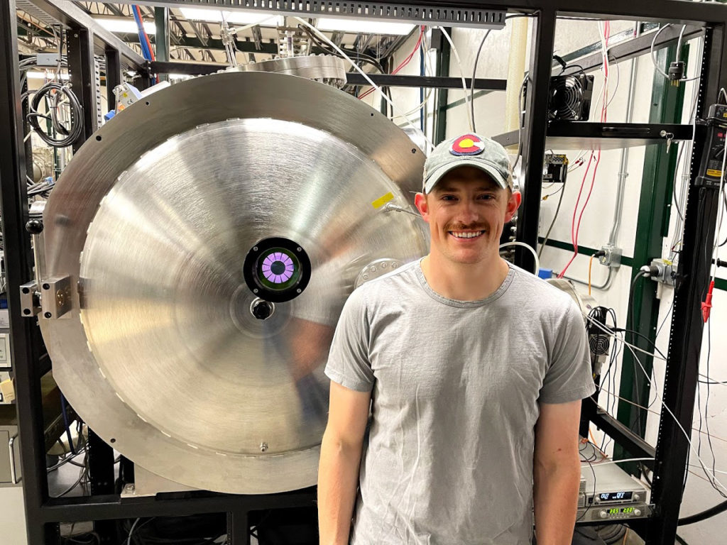 Seth Thompson stands next to a vacuum chamber, where testing a Low-Earth-Orbit (LEO) plasma source used to replicate plasma conditions experienced by spacecraft and other objects happens.