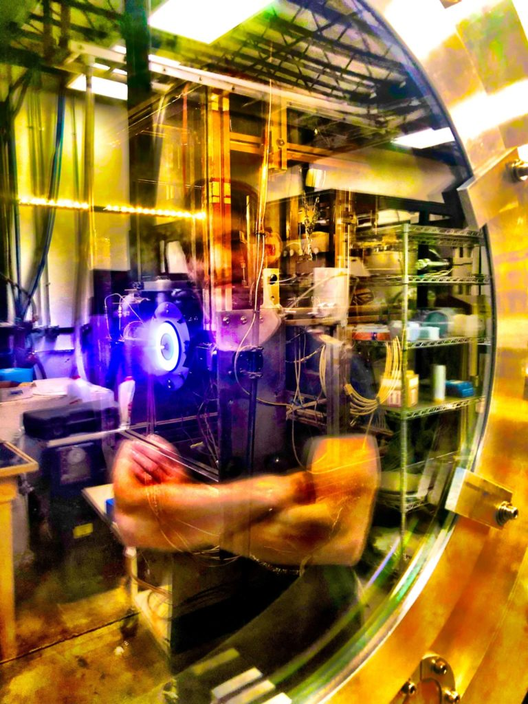 Reflection of graduate student Thomas Andreano as he watches his 2 kW Kr Hall thruster whose light is being transmitted through a window port of a large vacuum chamber at CSU. Photo credit: Professor John Williams