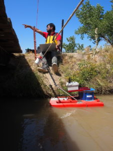 A researcher monitors sensor equipment on the edge of an irrigation canal.