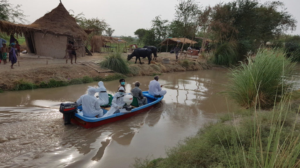 Photo of scientists in a boat applying polymer to the banks of an irrigation canal