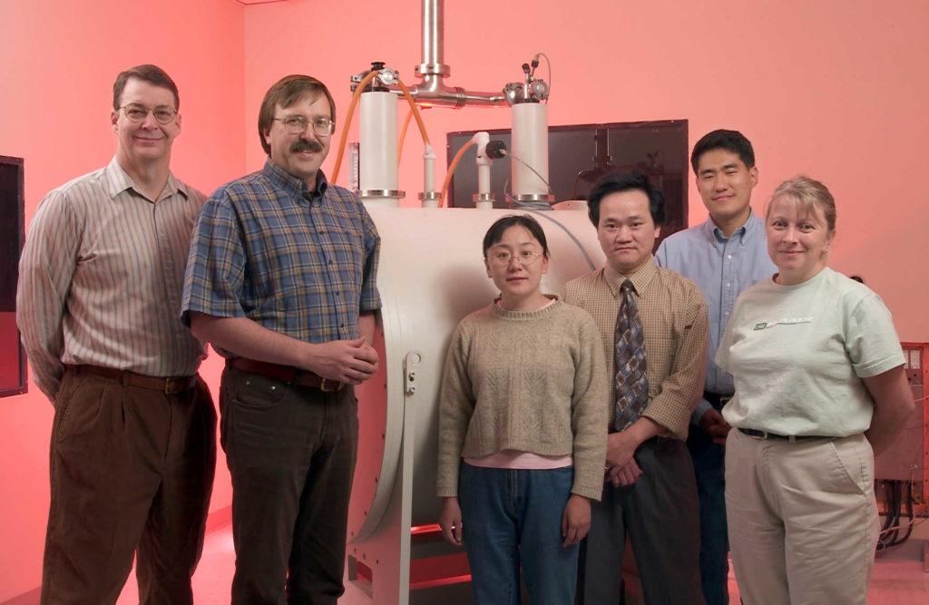 A picture of Professor Ted Watson with members of his lab team, circa 2003.