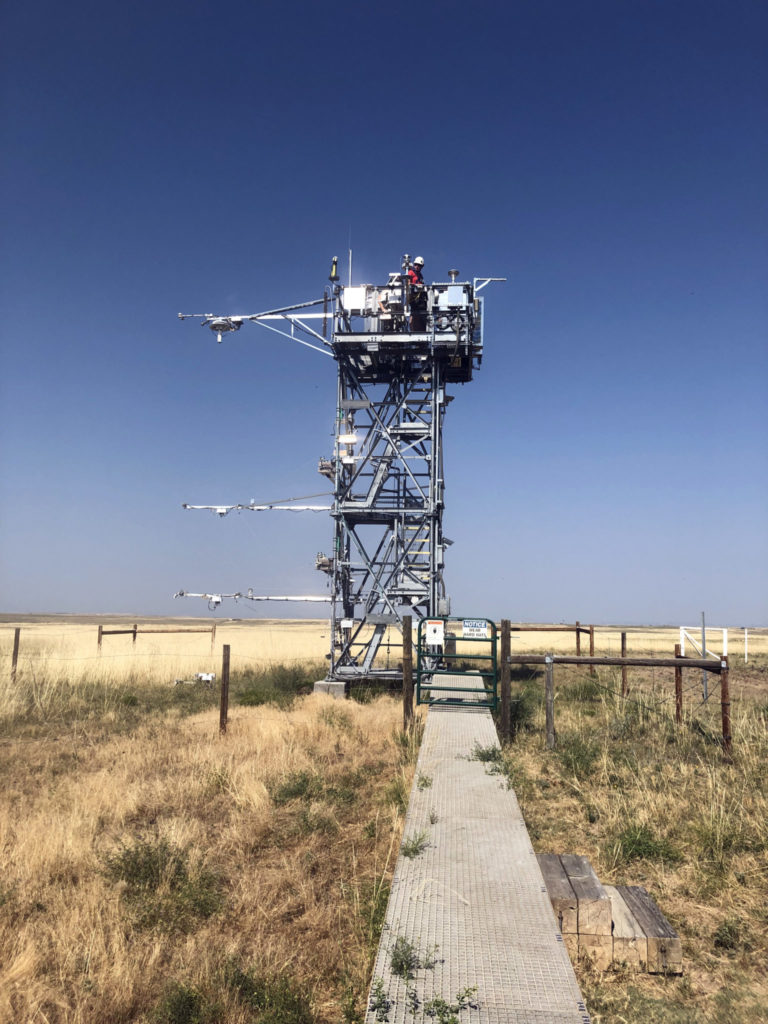 A scientist inspects instruments atop a tower at the Central Plains Experimental Range.